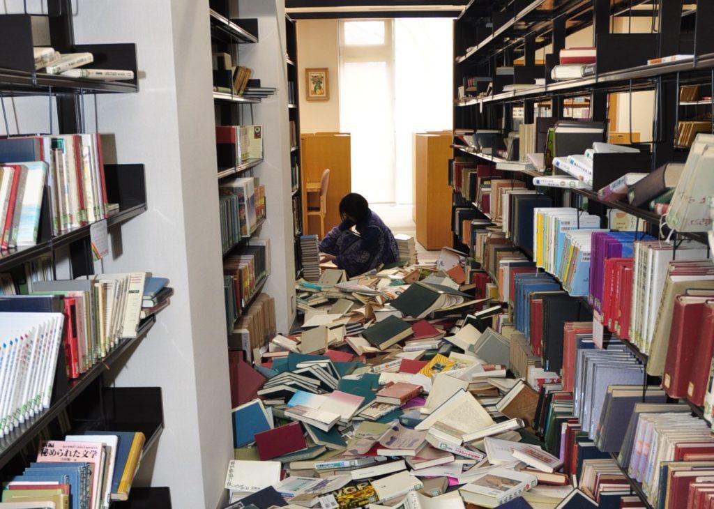 東日本大震災の翌日、図書館では本が見るも無残に崩れ落ちた状況。このほか体育館の天井や照明が落ちるなどの被害がありました。 平成23/3/13