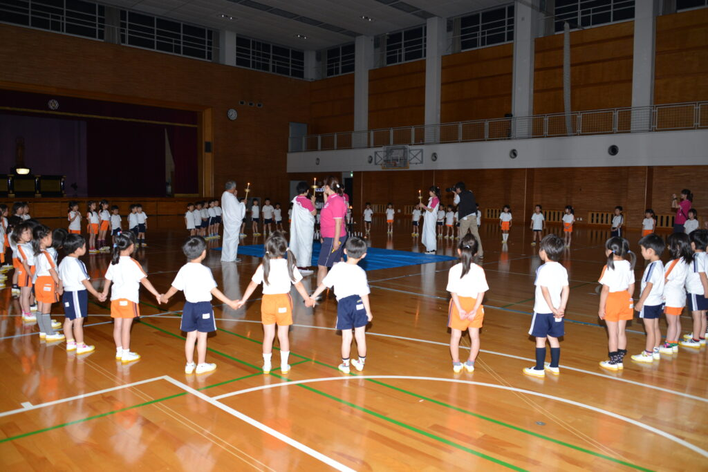 聖和幼稚園のお泊り会、夜のアリーナでのキャンドルサービスに子ども達も次第に静かになりました。平成25年7月19日<br />