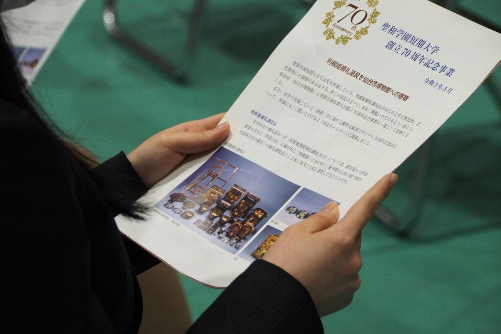 創立70周年記念事業のパンフレットを見る学生