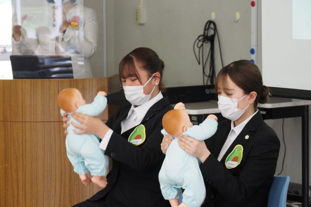 保育学科の模擬授業は「乳児保育」。わらべ歌に合わせて赤ちゃん人形と遊びました。