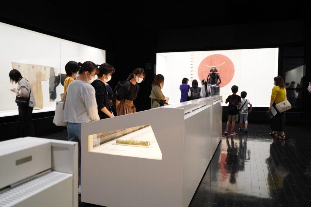 伊達政宗甲冑の前で展示を見る学生