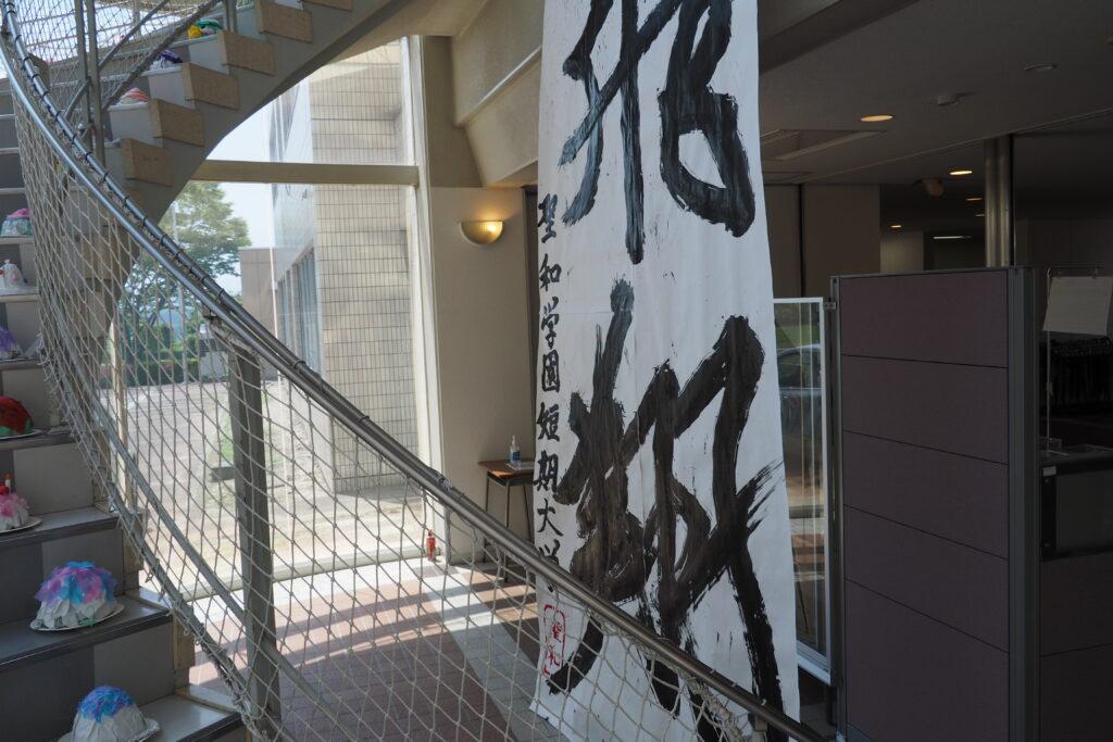 2階の会場に向かうらせん階段脇には、書道パフォーマンスの作品を掲示。