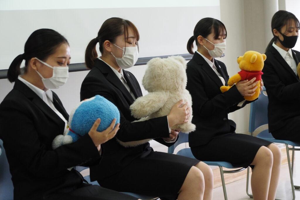 体験授業は「保育内容総論・わらべうた」。ぬいぐるみを幼児に見立てています。